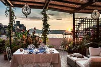Outdoor living and dining area on terrace with view of Lerici's castle and harbour at sunset