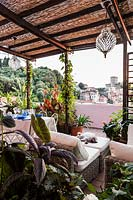 Outdoor living area under pergola on terrace with view of Lerici, Italy.