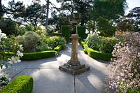Ornamental sundial at intersection of paths between Buxus edged borders.