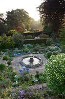 Overview of garden with rooms separated by yew hedges. Paving slab path between borders of shrubs and seating area beside water feature fountain.