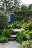 View up stone steps, through shrub borders to blue gate in wall in courtyard garden.