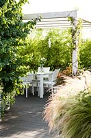 View along terrace with Stipa tenuissima and Parrota persica 'Vanessa' to a dining area under a pergola, screed with Phyllostachys nigra - Bamboo