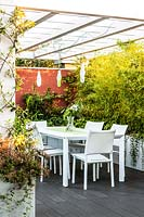 A dining area with lights suspended from pergola, screening from a trough of Phyllostachys nigra 'Epimedium'
