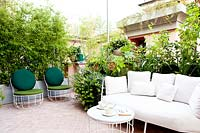A terrace wits tiled seating area screened by assorted plants including Phyllostachis nigra - Bamboo