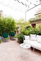 A terrace with tiled seating area screened by assorted plants including a Phyllostachis nigra - Bamboo