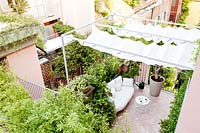 View of tiled terrace from the upper floor, showing shade canopy over seating area, railings and plant screening