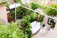 Small tiled terrace viewed from the house, a seating area with container plantings enclosed by metal railings