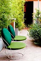 Two chairs on tiled terrace by house entrance, Bamboo plants in troughs provide a screen