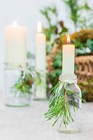 Candles in small glass bottles adorned with cut pine foliage
