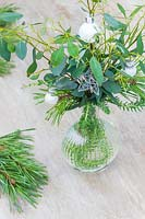 Table decoration featuring a glass vase filled with foliage decorated with silver stars and mini baubles