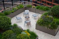 Looking down on roof garden showing paved seating areas surrounded by troughs of evergreens such as Hebe and Pinus with Gaura, Santolina and Lavendula