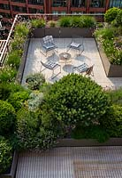 Looking down over paved roof garden showing seating area surrounded by troughs of evergreens such as Pinus - Pine, Hebe and perennials such as Gaura