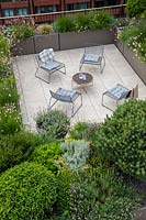 Over view of roof garden showing paved seating area enclosed with troughs of evergreen shrubs and perennials such as Gaura