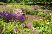 Wooden seats in The Perennial Meadow, at Scampston Hall Walled Garden, North Yorkshire, UK.