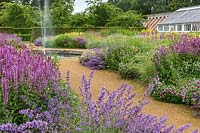 The Perennial Meadow with fountain at Scampston Hall Walled Garden, North Yorkshire, UK.