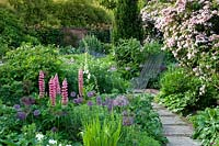 Cottage garden with pathway through mixed borders and metal reclining chair