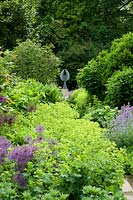 Alchemilla mollis in border leading to angel sculpture.