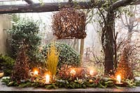 Outdoor table decoration made with Corylus avellana 'Contorta',  and branches of Abies nordmanniana, Picea pugnes 'Hopsii', Pittosporum tobira berries, pine cones, candles and mandarins