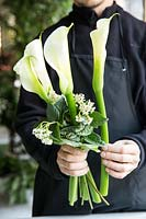 Creation of a wedding bouquet with calla, viburnum flowers and saxifrage leaves.