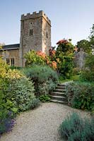 Gravel pathway to steps, also colourful shrub border and church beyond