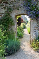 Stone arch in wall through to separate garden along a gravel path