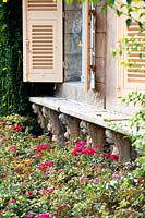 Carved stone window ledge beneath open shutters in old French house