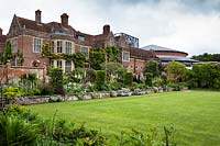 Mixed spring borders edging the lawn in front of Glyndebourne house