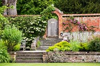 Walled garden with steps leading to a wooden garden gate, surrounding borders include Allium, rose 'luoise order' , hydrangea petiolaris.