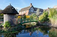 Monet bridge crosses the pond leads to a summerhouse, half-timbered house in background