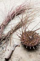 Piece of basketry near cutting tool and bundles of bare stems