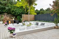 Sunken seating surrounded with wooden decking in modern garden.