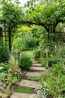 Stepping stones lead under the arch of a wooden pergola with Wisteria, borders of perennials and grasses in an informal cottage-garden style