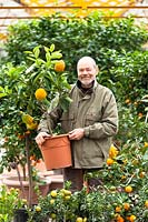 Man holding potted Citrus plant in a nursey