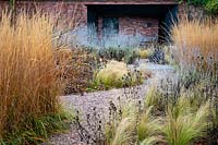Gravel path through winter beds of ornamental grasses.