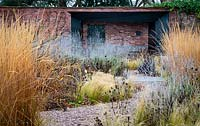 Gravel path through winter beds of ornamental grasses with garden wall, covered seating area and doorway.