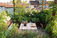 Garden table and chairs surrounded by dense planting on Italian city terrace.