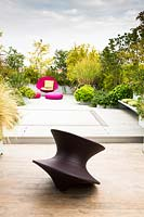 Relaxing area on a terrace with a Spun chair by Magis design in the foreground and mixed planting behind