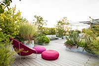 Terrace with decking and bright pink chair and cushions surrounded by autumnal shrubs and plants