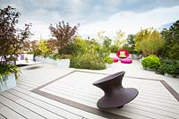 Terrace with decking and in the foreground Spun chair by Magis design, in the background a bright pink chair and cushions surrounded by shrubs