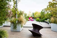 Relaxing area on a terrace with a Spun chair by Magis design in the foreground and mixed container planting behind
