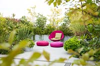 Relaxing area on a terrace with bright pink chair and cushions and mixed planting behind