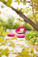 Relaxing area on a terrace viewed through shrubs. Mixed planting screens bright pink chair and cushions
