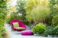 Bright pink wicker chair and cushion surrounded by container grown shrubs on a terrace. Stipa tenuissima e Lagestroemia 'Muskogee'.Erigeron karvinskianus  Rosmarinum officinalis, Pittosporum tobira nano, Miscanthus 'Morning Light' Spirea thumbergii, Amelanchier lamarkii, Osmanthus aquifolium.