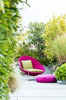 Relaxing area on a terrace with bright pink wicker chair and cushions and mixed planting behind