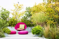 Relaxing area on a terrace with bright pink wicker chair and cushions and mixed planting behind screening the terrace
