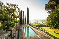 Overview of garden along terraces looking out on landscape, with swimming pool below and Cupressus sempervirens - Cypress - trees