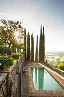 A swimming pool set in a terrace, views of Cupressus sempervirens - Cypress - trees and wider landscape