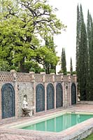 Swimming pool set in terrace with wall with trellis panels and alcove statue, Cupressus sempervirens - Cypress - trees