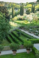 View over terraces on sloping landscape, includes edge of a parterre and orchards with Cupressus sempervirens - Cypress - trees beyond