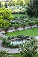 View over the centre of a parterre with grass beds and row of Citrus - Lemon - trees in pots, beyond another formal garden and orchard